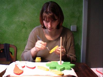 Frau bemalt Holzteile für einen Geburtstagskranz