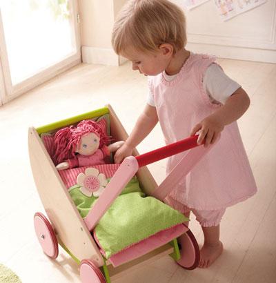 Mädchen umsorgt Puppe im Puppenwagen